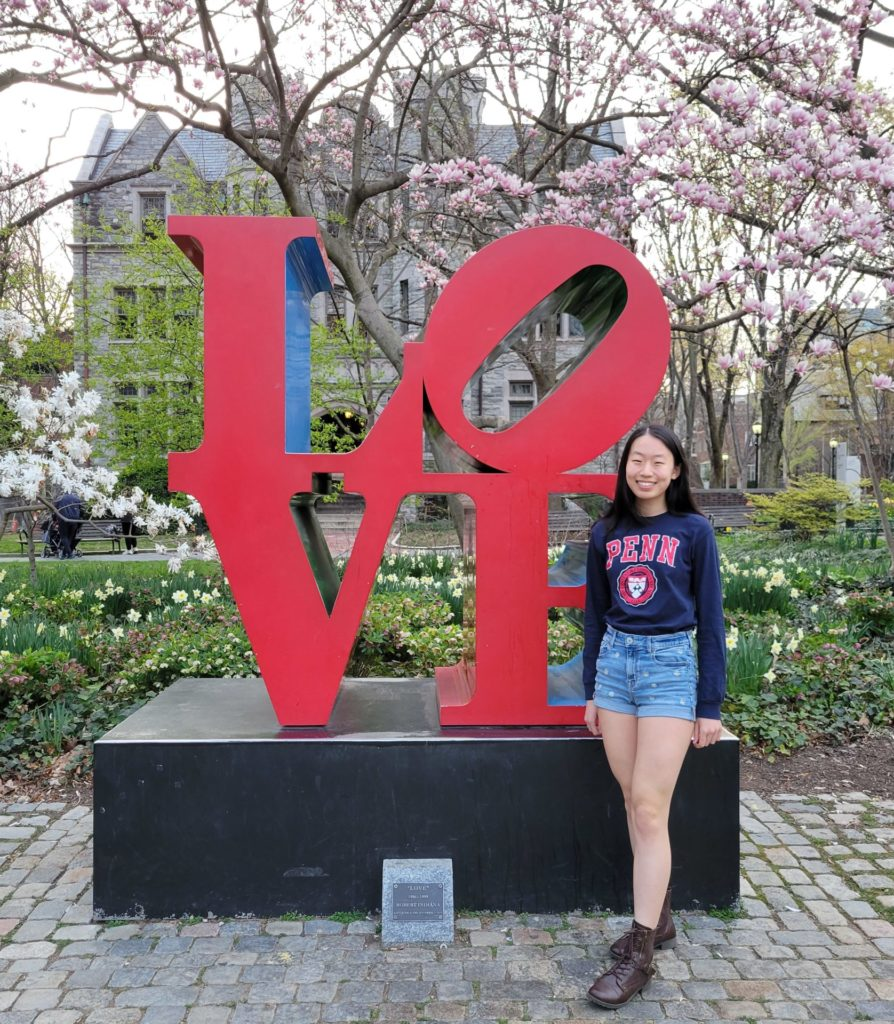 Annabelle Jin stands next to a sculpture made of the word love
