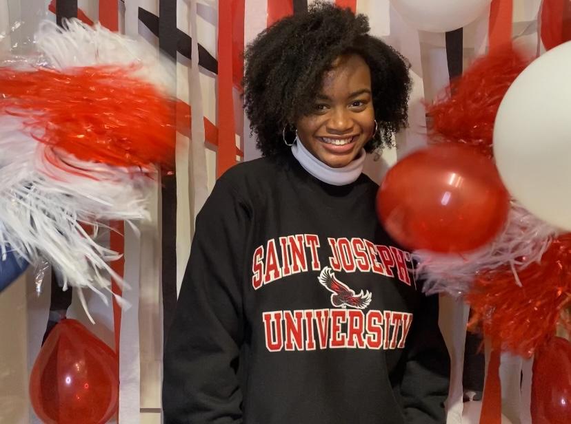 GLC graduate Sheridan Leak poses in a Saint Joseph's University sweatshirt in front of streamers and balloons