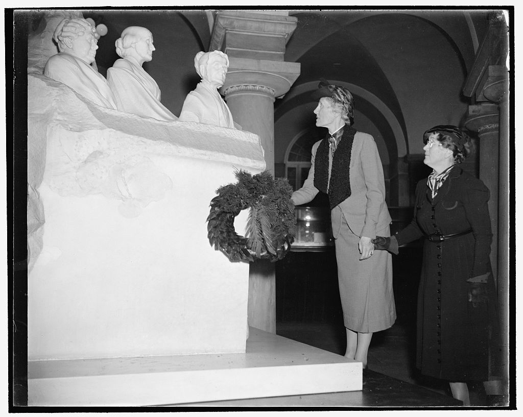 Two women laying a wreath in front of a statue composed of 3 busts of female suffragists