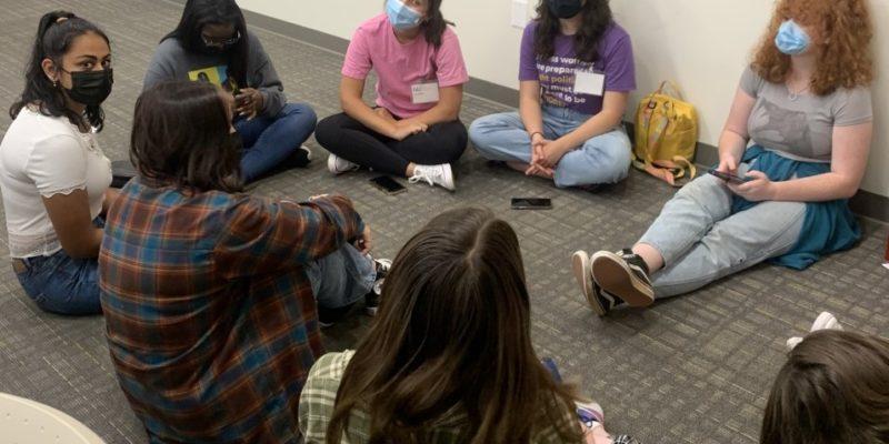 Group of teenage girls sitting in a circle talking